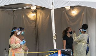 A nurse with the Washington, D.C. Dept. of Health, administers a COVID-19 test on F Street, Aug. 14, 2020, in Washington. This location tests approximately 450-500 people a week and has been open since June 1st. (AP Photo/Alex Brandon)