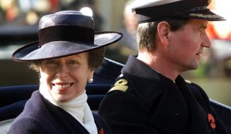 FILE - In this Nov. 6, 2001 file photo, Britain's Princess Anne with her husband Commander Tim Lawrence ride in a ceremonial carriage through Windsor town centre, where they were guests of Queen Elizabeth II at Windsor Castle to welcome King Abdullah and Queen Rania of Jordan on their state visit to England. Queen Elizabeth II's only daughter, Princess Anne, will be celebrating her 70th birthday on Saturday, Aug. 15, 2020 in a no-nonsense manner that befits her reputation in Britain. Whatever is planned for Saturday, it's certainly going to be a scaled-back affair because of the coronavirus pandemic. (AP Photo/Dave Caulkin/File)
