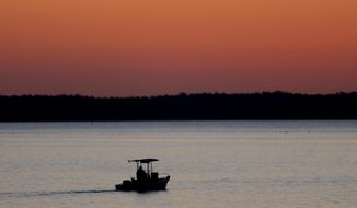 FILE - In this May 14, 2020 file photo, a small boat chugs along the Honga River near the Chesapeake Bay as the sky lights up at sunrise, in Fishing Creek, Md. Researchers are predicting a slightly smaller-than-average oxygen dead zone in the Chesapeake Bay this year. One of the main reasons why is because there was less rainfall washing pollution off of farms and cities and into the nation's largest estuary. The forecast was released Wednesday, June 17 by researchers from the University of Michigan, the University of Maryland and the Chesapeake Bay Program.  (AP Photo/Julio Cortez, File)
