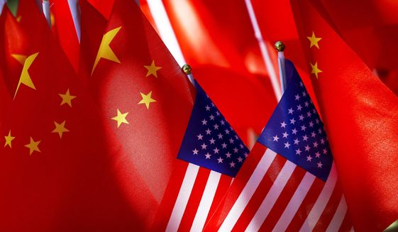 """FILE - In this Sept. 16, 2018, file photo, American flags are displayed together with Chinese flags on top of a trishaw in Beijing. China says Friday, Aug. 14, 2020, the United States is trying to """"demonize and stigmatize"""" bilateral its foreign relations, in a scathing attack on the Trump administration's designation of the Confucius Institute U.S. Center as a foreign mission of the Chinese Communist Party. (AP Photo/Andy Wong, File)"""