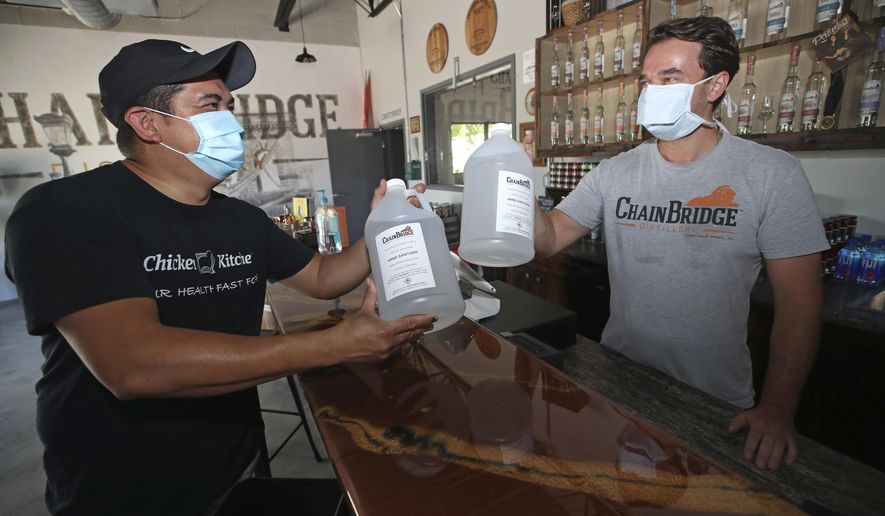 Chicken Kitchen owner Julio Salazar, left, buys hand sanitizer from Chainbridge Distillery owner Bela Nahori in Oakland Park, Fla., on Tuesday, Aug. 11, 2020. The local distillery was given FDA approval to stop making spirits and instead make hand sanitizer at the start of the pandemic, but the demand has since plummeted and Nahori is currently overstocked.  (John McCall /South Florida Sun-Sentinel via AP)
