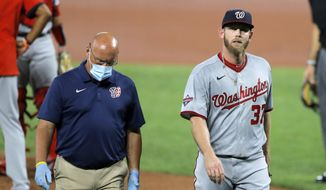 Washington Nationals starting pitcher Stephen Strasburg, right, walks with a member of the training staff as he heads to the dugout after leaving the game during the first inning of a baseball game against the Baltimore Orioles, Friday, Aug. 14, 2020, in Baltimore. (AP Photo/Julio Cortez)  **FILE**
