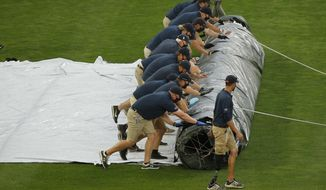 Minnesota Twins grounds crew members roll out a tarp for expected rain which has delayed the start of a baseball game with the Kansas City Royals on Friday, Aug. 14, 2020, in Minneapolis. (AP Photo/Bruce Kluckhohn)