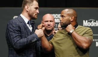 FILE - In this Thursday, July 5, 2018, filer photo, Stipe Miocic, left, and Daniel Cormier pose during a news conference for UFC 226 in Las Vegas. The trilogy fight between Daniel Cormier and champ Stipe Miocic will crown the greatest heavyweight of all time. UFC 252 Saturday, Aug. 15, 2020, in Las Vegas could be Cormier's last fight ever.  (AP Photo/John Locher)
