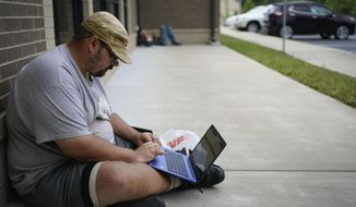 Barlow Mitchell sits outside the Lee County Public Library while using the public WIFI, in Beattyville, Ky., Wednesday, July 29, 2020. As in other places, parents and officials are concerned about the virus, but dramatically limited internet access in many rural places also means kids could fall seriously behind if the pandemic keeps them home again. (AP Photo/Bryan Woolston)