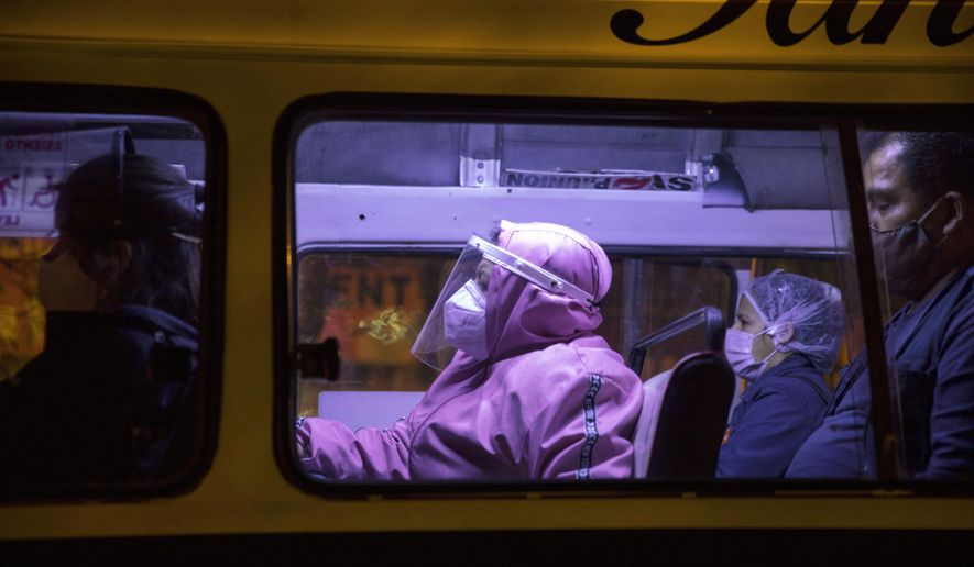 Commuters using protective gear amid the coronavirus pandemic sit inside a public bus in Lima, Peru, Thursday, Aug. 13, 2020. (AP Photo/Rodrigo Abd)