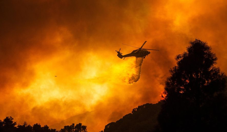 In this Aug. 12, 2020, file photo, a helicopter drops water on the Lake Hughes Fire in Angeles National Forest north of Santa Clarita, Calif. (AP Photo/Ringo H.W. Chiu, File)