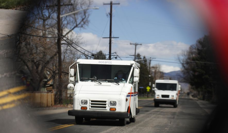 FILE - In this March 31, 2020, file photo United States Post Office delivery trucks are reflected in the side mirror of a vehicle as postal delivers set off on their daily rounds in Arvada, Colo. The U.S. Postal Service is warning states that it cannot guarantee all ballots cast by mail for the November election will arrive in time to be counted, even if mailed by state deadlines. (AP Photo/David Zalubowski, File)