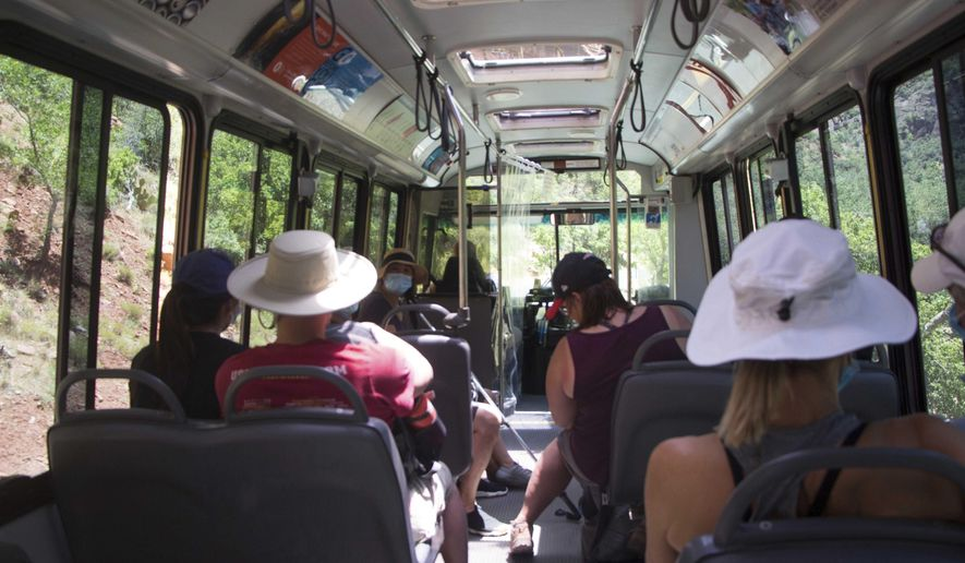 Visitors to Zion National Park, Utah ride a shuttle bus on Wednesday, July 1, 2020. Now two decades old, the buses are falling apart but there is no money to replace them. (K. Sophie Will/The Spectrum via AP)