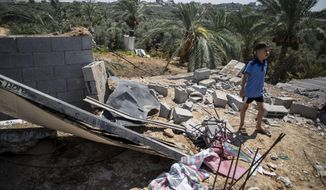 A Palestinian boy inspects the damage in his family home following Israeli airstrikes in Buriej refugee camp, central Gaza Strip, Saturday, Aug. 15, 2020. (AP Photo/Khalil Hamra)