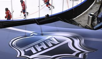 An NHL logo is displayed as Washington Capitals players skate prior to NHL Eastern Conference Stanley Cup playoff hockey action against the New York Islanders in Toronto, Friday, Aug. 14, 2020. The NHL is providing its playoff teams a few tastes of home in their respective hub cities. Teams are hearing their pre-game warm-up music, goal songs and national anthem performers. Crowd noise is being piped in and new camera angles have been added for a TV audience. (Nathan Denette/The Canadian Press via AP)