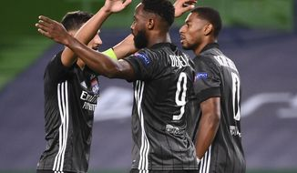 Lyon's Moussa Dembele, centre, celebrates with teammates after scoring his team's third goal during the Champions League quarterfinal match between Manchester City and Lyon at the Jose Alvalade stadium in Lisbon, Portugal, Saturday, Aug. 15, 2020. (Franck Fife/Pool Photo via AP)