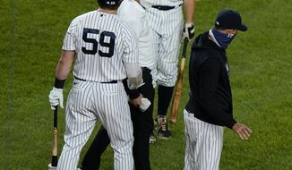 A trainer checks on New York Yankees' DJ LeMahieu, above, during his at bat during the sixth inning of a baseball game against the Boston Red Sox Saturday, Aug. 15, 2020, in New York. LeMahieu later left the game with due to injury. The Yankees won 11-5. (AP Photo/Frank Franklin II)