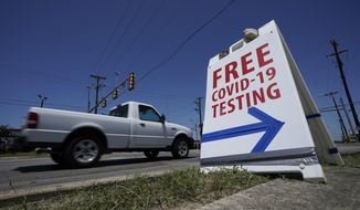 A truck passes a sign for free COVID-19 testing, Friday, Aug. 14, 2020, in San Antonio.  (AP Photo/Eric Gay)  **FILE**