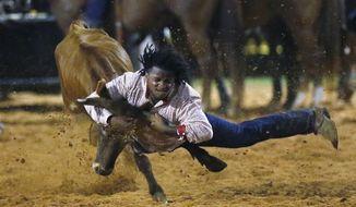 Dorian Autman competes in the Bull Doggin event at the 65th annual Okmulgee Roy LeBlanc Invitational Rodeo, the nation's oldest all-black professional rodeo event, in Okmulgee, Okla., Saturday, Aug. 8, 2020. (AP Photo/Sue Ogrocki)