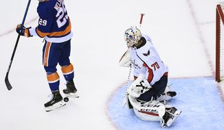 New York Islanders center Brock Nelson (29) tries to tip the puck past Washington Capitals goaltender Braden Holtby (70) during second-period NHL Eastern Conference Stanley Cup playoff hockey action in Toronto, Sunday, Aug. 16, 2020. (Nathan Denette/The Canadian Press via AP)