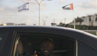 A man gives a thumbs up as he passes United Arab Emirates and Israeli flags at the Peace Bridge in Netanya, Israel, Sunday, Aug. 16, 2020. The UAE flag was displayed to celebrate last week's announcement that Israel and the United Arab Emirates have agreed to establish full diplomatic relations. (AP Photo/Ariel Schalit)