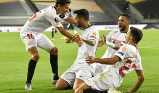 Sevilla's Suso, second from left, celebrates with his teammates after he scored his side's first goal during an Europa League semifinal match between Sevilla and Manchester United, in Cologne, Germany, Sunday, Aug. 16, 2020. (AP Photo/Martin Meissner, Pool)