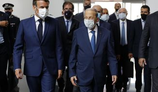 French President Emmanuel Macron, left, and Lebanese President Michel Aoun walk side by side at Beirut airport, Lebanon, Thursday Aug.6, 2020. French President Emmanuel Macron has arrived in Beirut to offer French support to Lebanon after the deadly port blast.(AP Photo/Thibault Camus, Pool)