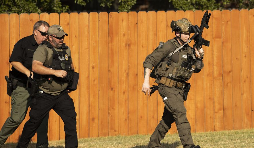 Police officers work near the house in Cedar Park, Texas, where a person remained barricaded Sunday, Aug. 16, 2020. Three police officers were shot, authorities said. The officers are in stable condition at a local hospital, police said on Twitter. (Jay Janner/Austin American-Statesman via AP)