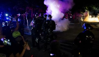 Police deploy smoke canisters at SE Ankeny and Cesar Chavez Blvd. Police declared a riot around midnight as Portland protests continued for the 80th consecutive night Saturday, Aug. 15, 2020. Protesters gathered at Laurelhurst Park Saturday evening before marching to the Penumbra Kelly building.  (Dave Killen/The Oregonian via AP)
