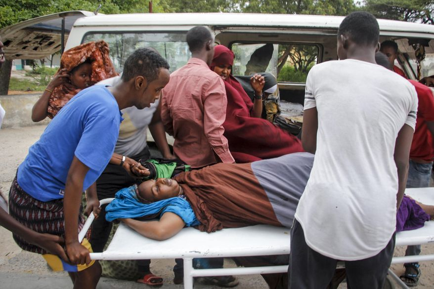 Medical workers and other Somalis help a civilian woman, who was wounded when a powerful car bomb blew off the security gates to the Elite Hotel, as she arrives at a hospital in Mogadishu, Somalia Sunday, Aug. 16, 2020. A Somali police officer says at least 10 people have been killed and more than a dozen others injured in an ongoing siege at the beachside hotel in Somalia's capital where security forces are battling Islamic extremist gunmen who have invaded the building. (AP Photo/Farah Abdi Warsameh)