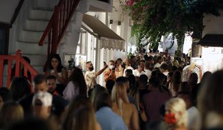 People gather at the narrow streets of Matogiannia after the bars closed at midnight on the Aegean Sea island of Mykonos, Greece, early Sunday, Aug. 16, 2020. The Greek government has been worried about the recent surge in coronavirus cases that threatens to undo its initial success in keeping infections and deaths at low levels. On the island of Mykonos, an internationally famous tourist destination, restaurants, bars and cafes were forced on Aug. 11 to close at midnight, and not to reopen until 7 a.m. (AP Photo/Thanassis Stavrakis)