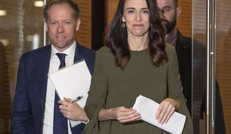New Zealand Prime Minister Jacinda Ardern, center, arrives to announce a new date for national elections, at a news conference in Wellington, New Zealand, Monday, Aug. 17, 2020. The election had been scheduled for Sept. 19 but will now be held on Oct. 17, after a COVID-19 outbreak in Auckland. (Mark Mitchell/New Zealand Herald via AP)