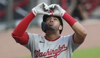 Washington Nationals' Luis Garcia reacts after hitting a two-run home run against the Atlanta Braves during the second inning of a baseball game on Monday, Aug. 17, 2020, in Atlanta.  Garcia became the first player born in the 2000s to hit a homer in the big leagues. The 20-year-old second baseman made history with a two-run shot into the right-field seats off Atlanta's Touki Toussaint in the second inning. (Curtis Compton/Atlanta Journal-Constitution via AP)