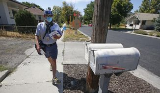 A U.S. Postal Service carrier delivers mail to homes Monday, Aug. 17, 2020, in Salt Lake City. (AP Photo/Rick Bowmer)
