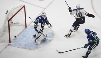 Vancouver Canucks goalie Jacob Markstrom (25) gives up a goal to St. Louis Blues' Brayden Schenn (10) as Troy Stecher (51) defends during overtime in Game 3 of an NHL hockey first-round playoff series, Sunday, Aug. 16, 2020, in Edmonton, Alberta. (Jason Franson/The Canadian Press via AP)