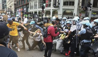 Chicago police use pepper spray on protesters at the corner of Randolph and Dearborn streets in downtown Chicago on Saturday, Aug. 15, 2020. The protesters are looking to defund the Chicago Police Department and to abolish ICE. (Chris Sweda/Chicago Tribune via AP)