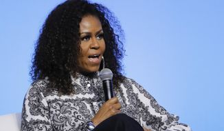 In this Dec. 12, 2019, file photo former first lady Michelle Obama speaks during an event for Obama Foundation in Kuala Lumpur, Malaysia. An adviser to Michelle Obama says the former first lady will stress Democrat Joe Biden's competency and character in Monday night's keynote address at the party's virtual nominating convention (AP Photo/Vincent Thian, File)