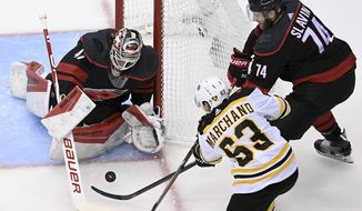 Carolina Hurricanes goaltender James Reimer (47) makes a save on a shot from Boston Bruins left wing Brad Marchand (63) as Hurricanes defenseman Jaccob Slavin (74) looks on during first-period NHL Eastern Conference Stanley Cup playoff hockey action in Toronto, Monday, Aug. 17, 2020. (Nathan Denette/The Canadian Press via AP)