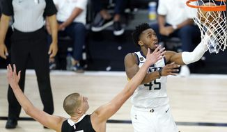 Utah Jazz's Donovan Mitchell, right, goes up for a shot against Denver Nuggets' Nikola Jokic during the second half of an NBA basketball first round playoff game, Monday, Aug. 17, 2020, in Lake Buena Vista, Fla. (AP Photo/Ashley Landis, Pool)