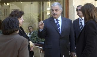 In this Feb. 14, 2005, file photo, former Lebanese Prime Minister Rafik Hariri, center, speaks to people outside the Lebanese Parliament minutes before an explosion killed him and 22 others, in Beirut, Lebanon. More than 15 years after the truck bomb assassination of Hariri in Beirut, a U.N.-backed tribunal in the Netherlands is announcing verdicts this week in the trial of four members of the militant group Hezbollah allegedly involved in the killing. (AP Photo, File)