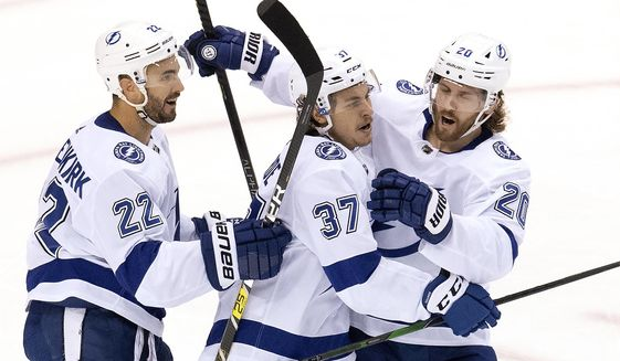 Tampa Bay Lightning center Yanni Gourde (37) is congratulated on his goal by defenseman Kevin Shattenkirk (22) and center Blake Coleman (20) after scoring against the Columbus Blue Jackets during the second period of NHL Eastern Conference Stanley Cup first round playoff hockey action in Toronto, Monday, Aug. 17, 2020. (Frank Gunn/The Canadian Press via AP)