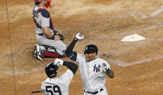 New York Yankees' Aaron Hicks, right, celebrates with teammate Luke Voit (59) after hitting a solo home run during the seventh inning of a baseball game against the Boston Red Sox, Monday, Aug. 17, 2020, in New York. Red Sox catcher Kevin Plawecki, top, looks on. (AP Photo/Kathy Willens)
