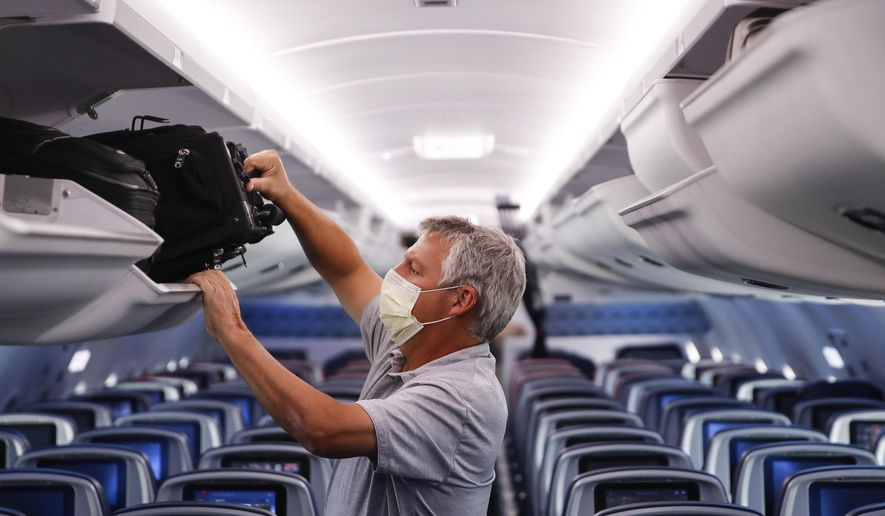 In this May 28, 2020, file photo, a passenger wears personal protective equipment on a Delta Airlines flight after landing at Minneapolis−Saint Paul International Airport, in Minneapolis. (AP Photo/John Minchillo, File)