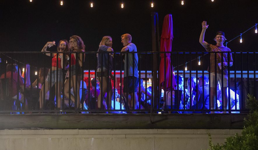 Patrons stand on the Bear Trap's rooftop bar on The Strip, the University of Alabama's bar scene, Saturday, Aug. 15, 2020, in Tuscaloosa, Ala. More than 20,000 students returned to campus for the first time since spring break, with numerous school and city codes in effect to limit the spread of COVID-19. (AP Photo/Vasha Hunt)