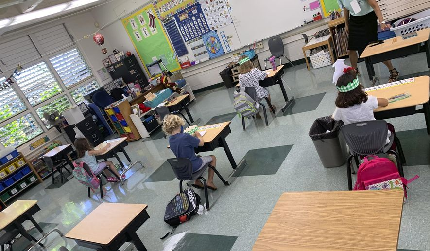 In this photo provided by Keoki Fraser, a small group of kindergarteners sits spaced apart in a classroom at Aikahi Elementary School in Kailua, Hawaii on Monday, Aug. 17, 2020. (Keoki Fraser via AP)  **FILE**
