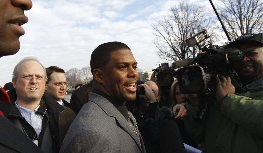 FILE - In this Jan. 19, 2011, file photo, Arizona Cardinals running back Jason Wright, center, talks to the media on Capitol Hill in Washington. The Washington Football Team has hired Jason Wright as team president. He's the first Black person to hold this job in NFL history and at 38 becomes the youngest team president in the league. (AP Photo/Alex Brandon, File)