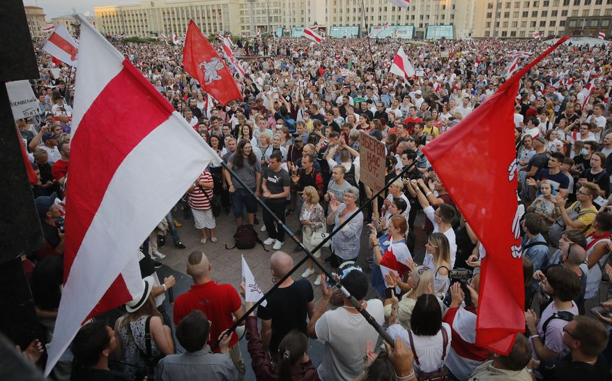 Belarusian opposition supporters gather for a protest rally in front of the government building at Independent Square in Minsk, Belarus, Tuesday, Aug. 18, 2020. Workers at more state-controlled companies and factories took part in the strike that began the day before and has encompassed several truck and tractor factories, a huge potash factory that accounts for a fifth of the world's potash fertilizer output and is the nation's top cash earner, state television and the country's most prominent theater. (AP Photo/Dmitri Lovetsky)