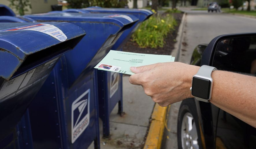 """In this file photo, a person drops into a mail box applications for mail-in ballots, in Omaha, Neb., Tuesday, Aug. 18, 2020. The Postmaster general announced Tuesday he is halting some operational changes to mail delivery that critics warned were causing widespread delays and could disrupt voting in the November election. Postmaster General Louis DeJoy said he would """"suspend"""" his initiatives until after the election """"to avoid even the appearance of impact on election mail."""" (AP Photo/Nati Harnik)  **FILE**"""