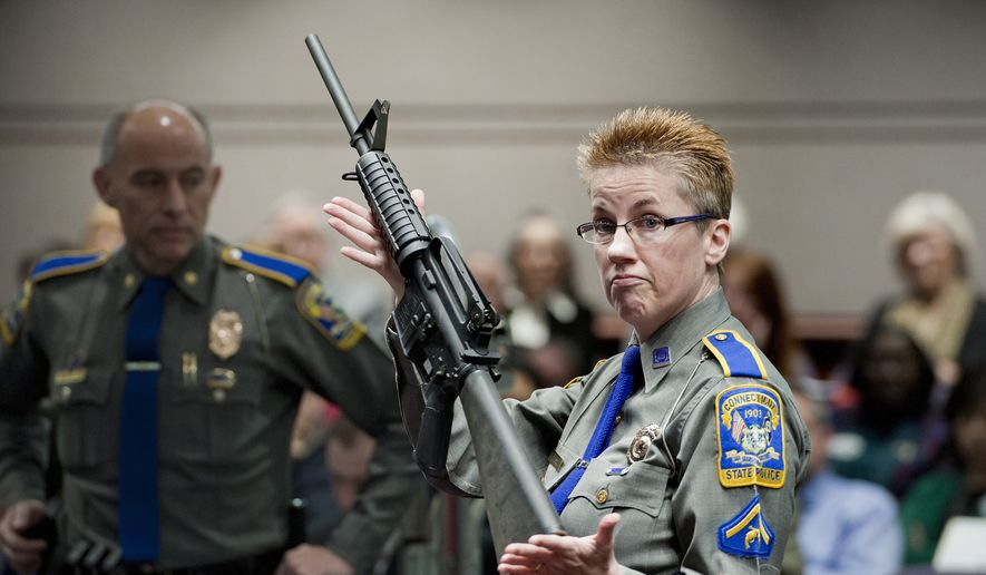 In this Jan. 28, 2013, file photo, firearms training unit Detective Barbara J. Mattson, of the Connecticut State Police, holds up a Bushmaster AR-15 rifle made by Remington Arms, the same make and model of the gun used by Adam Lanza in the December 2012 Sandy Hook School shooting, during a hearing of a legislative subcommittee in Hartford, Conn. On Tuesday, Aug. 18, 2020, a lawyer for some of the Sandy Hook school shooting victims accused Remington Arms of using its new bankruptcy case to try to wipe out the families' lawsuit against the company over how it marketed the rifle used in the massacre. (AP Photo/Jessica Hill, File)