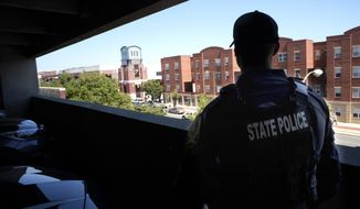 A Virginia State Trooper stands in a parking deck overlooking the Siegel Center in Richmond, Va., where the Virginia House of Delegates is meeting Tuesday, August 18, 2020. (Bob Brown/Richmond Times-Dispatch via AP)