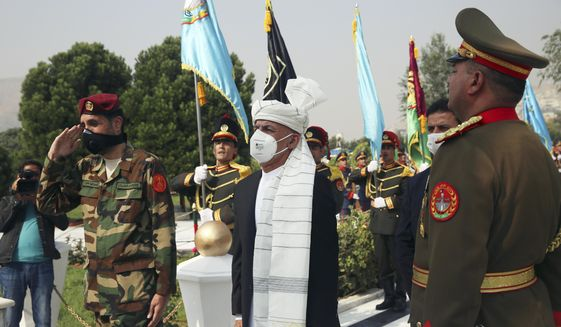Afghan President Ashraf Ghani sings the national anthem after laying flowers on the Independence Minaret monument during the Independence Day celebrations at the Defense Ministry in Kabul, Afghanistan, Tuesday, Aug. 18, 2020. (AP Photo/Rahmat Gul)