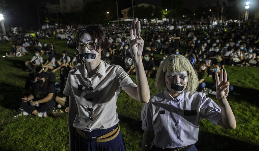 Pro-democracy students with tape covering their mouths raise a three-finger salute, a symbol of resistance, during a protest rally at Mahidol University in Nakhan Pathom, Thailand, Tuesday, Aug. 18, 2020. Student protesters have stepped up pressure on the government with three core demands: holding new elections, amending the constitution and ending the intimidation of critics of the government. (AP Photo/Gemunu Amarasinghe)