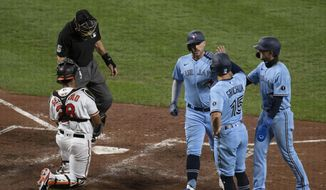 Toronto Blue Jays third baseman Travis Shaw, left, celebrates with Randal Grichuk, center,  and Cavan Biggio, right, at home plate after hitting a three-run home run during the fifth inning of a baseball game against the Baltimore Orioles, Tuesday, Aug. 18, 2020, in Baltimore. (AP Photo/Tommy Gilligan)