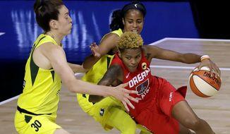 Atlanta Dream guard Courtney Williams (10) drives into Seattle Storm guard Jordin Canada (21) and forward Breanna Stewart (30) during the first half of a WNBA basketball game Wednesday, Aug. 12, 2020, in Bradenton, Fla. (AP Photo/Chris O'Meara)